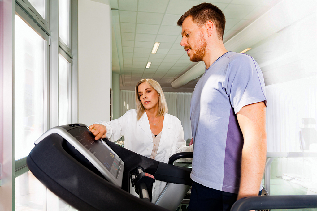 athlete on the treadmill he performs the instructions of physical therapist who assists him. in the background other athletes