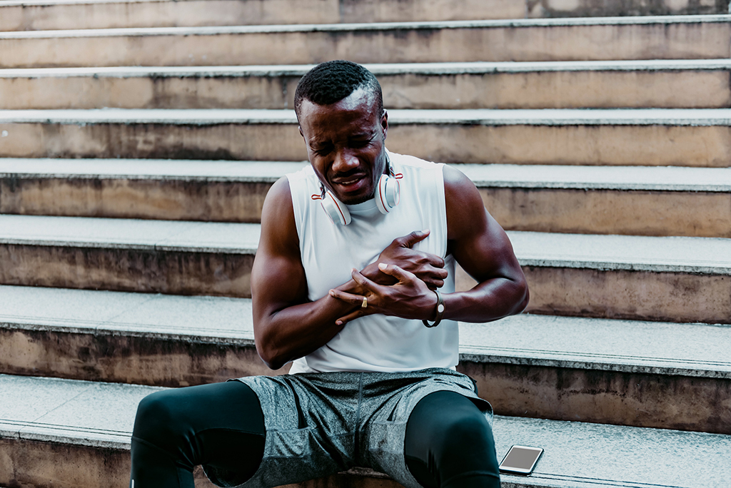 A 31 year old African American man with black skin he is and athlete, He is having pain in the chest due to heart disease, After he exercised by running up and down the stairs, to health care concept
