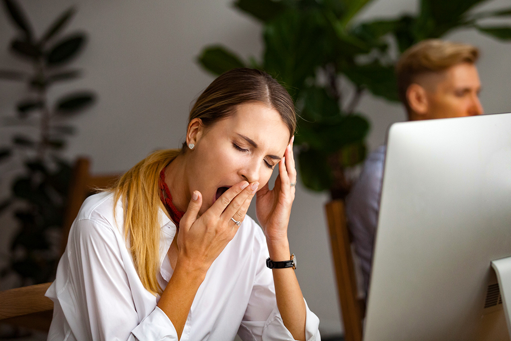 Bored businesswoman yawning at workplace feeling no motivation or lack of sleep tired of boring office routine, exhausted restless employee gaping suffering from chronic fatigue or overwork concept