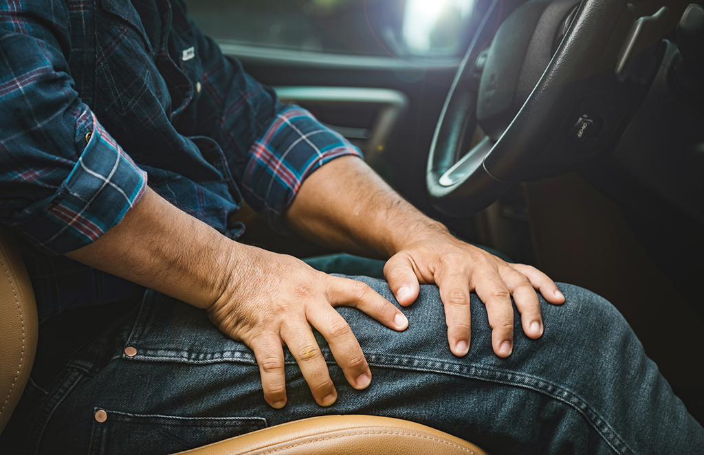 Injury or tired from long driving concept : Man use hands to hold and massage on his Thigh in the car while stop. Outdoor shooting for transport and healthcare