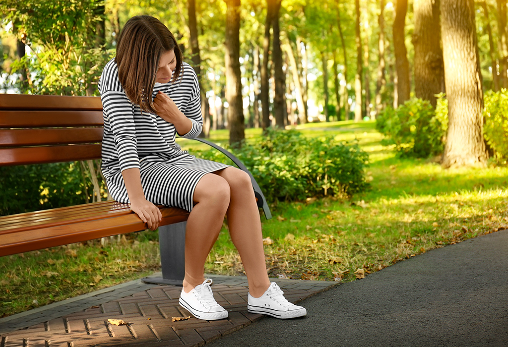 Young woman suffering from heart attack outdoors