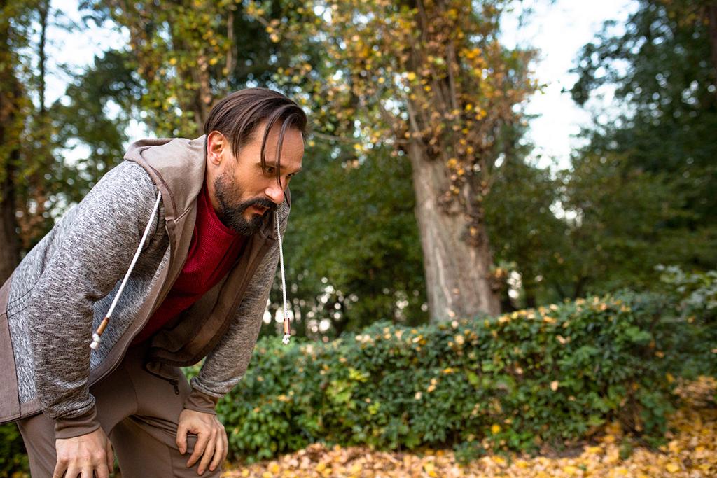 Man having short rest to take a breath after running in urban park. Adult man having rest after jogging.